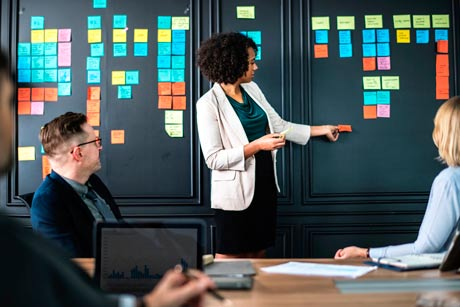 businessmen having meeting in front of whiteboard with sticky notes