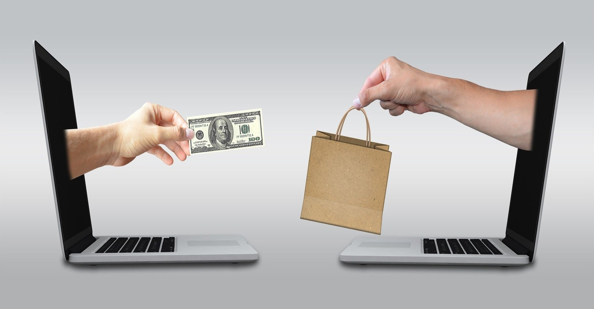 Two arms extending out of two laptops to exchange goods with money