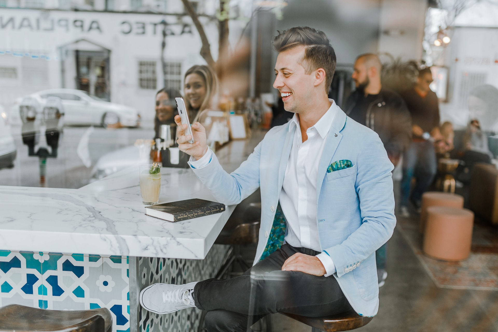 A young man in a blue sport jacket smiling and using his smartphone in a cafe