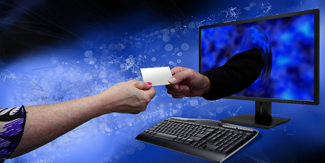 Two hands exchanging a white piece of paper through a computer
