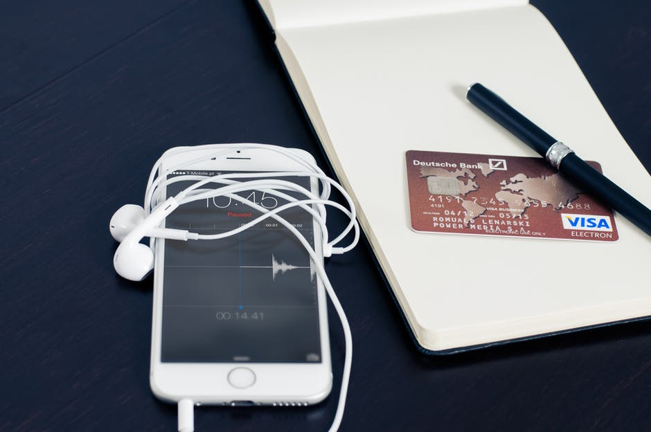 iphone with white headphones and notepad with credit card laying on a desk
