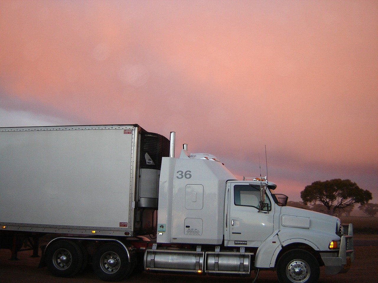 A white truck transporting cargo during sunset