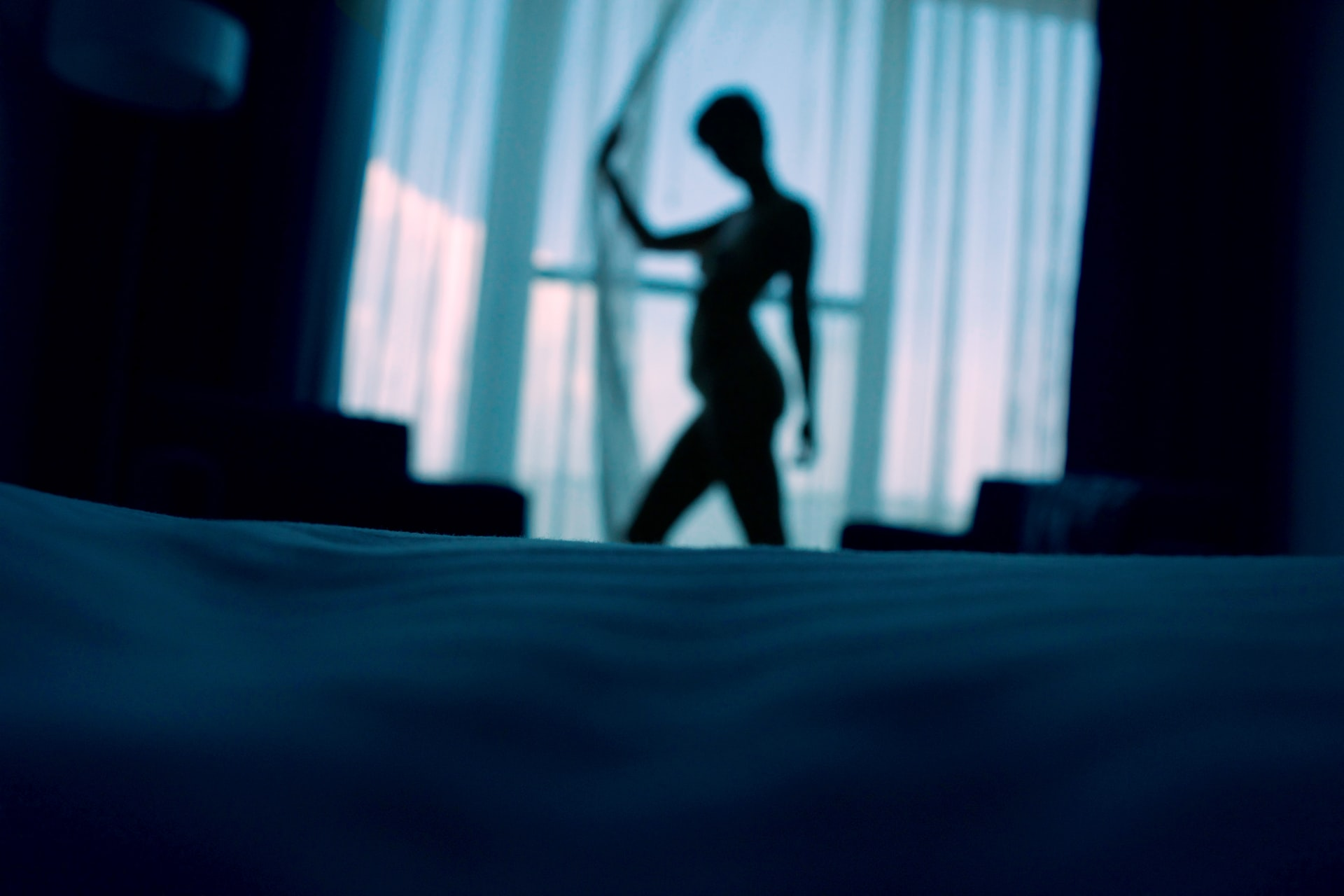 Silhouette of a nude woman standing in front of balcony curtains