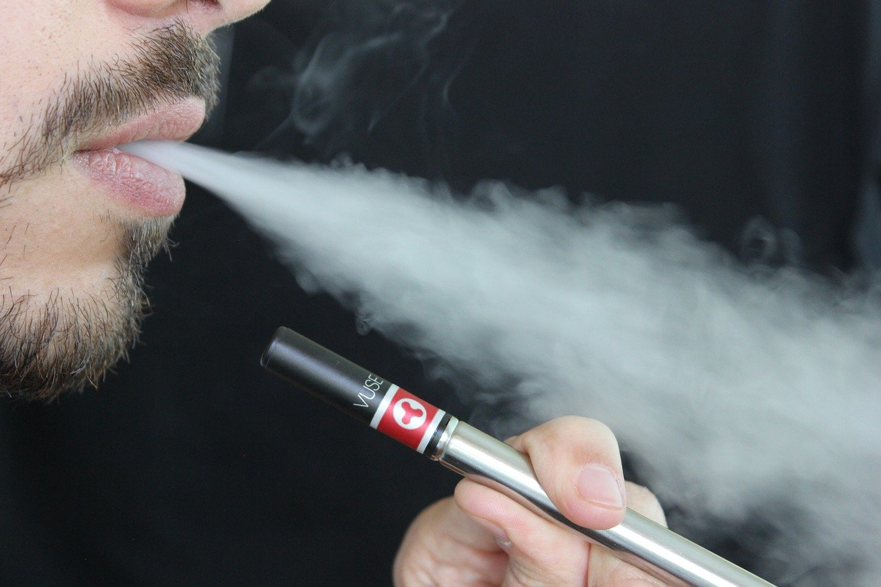 A young man exhaling smoke from an e-cigarette
