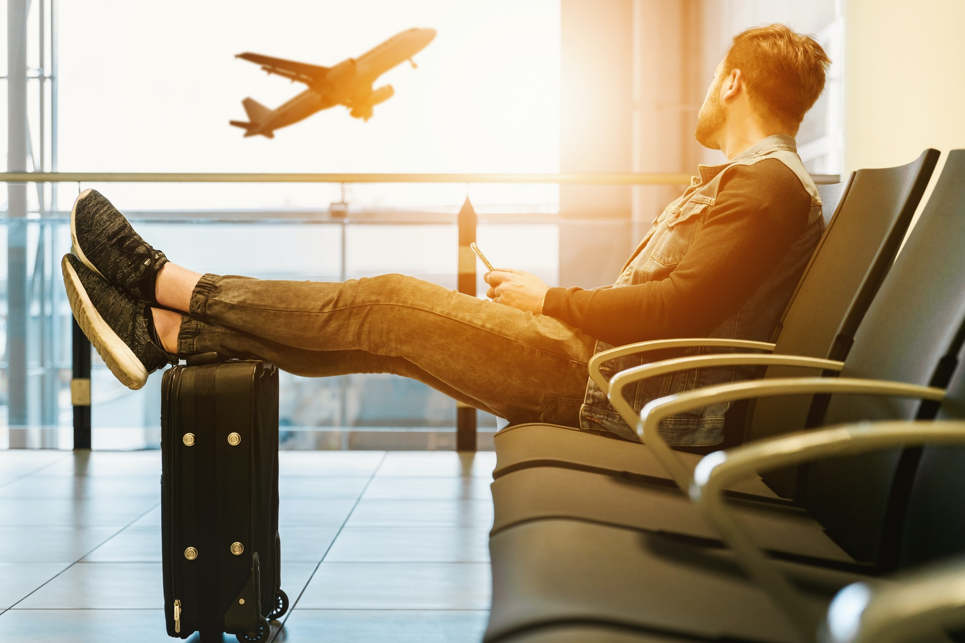 Man sitting in an airport with feet on his luggage looking at an ascending plane
