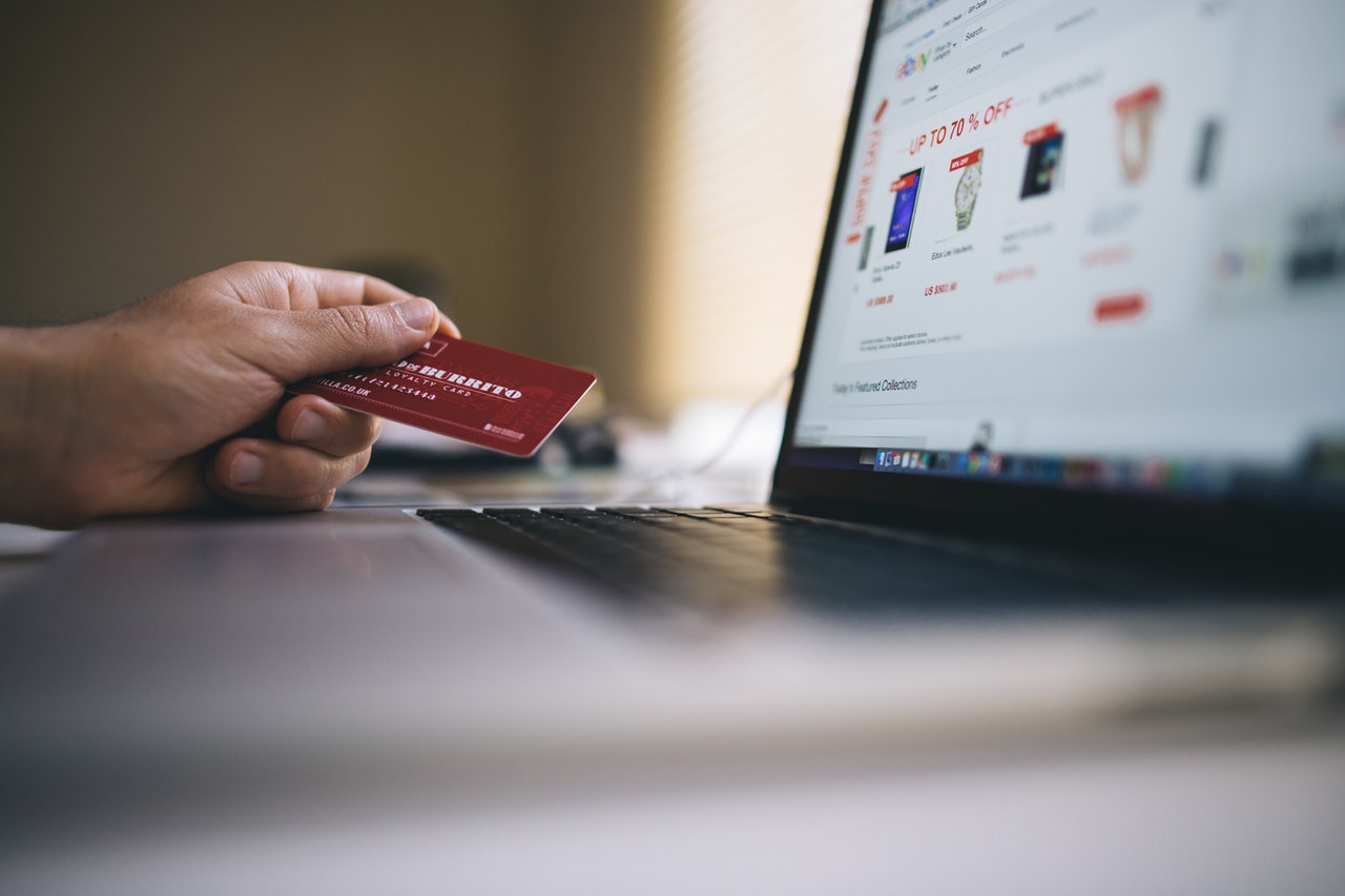 Person's hand holding a credit card as a payment solution for purchase on their macbook