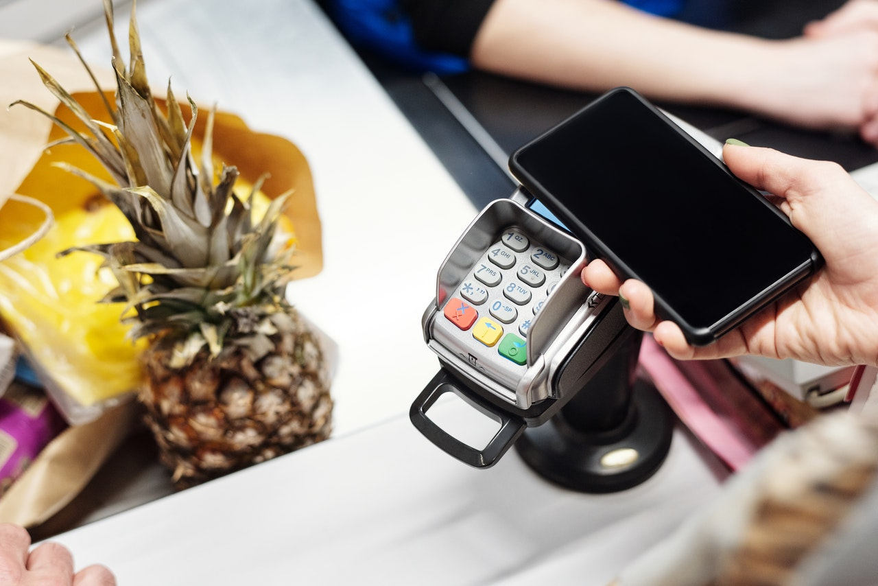 Hand swiping smartphone payment solution across a card reader File name: smartphone-swiping-card-reader
