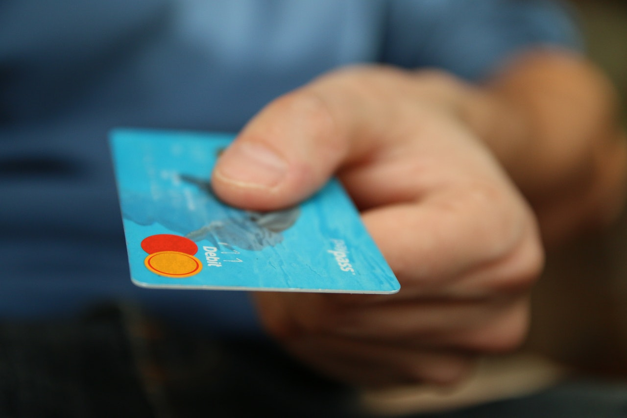 Hand holding out a credit card