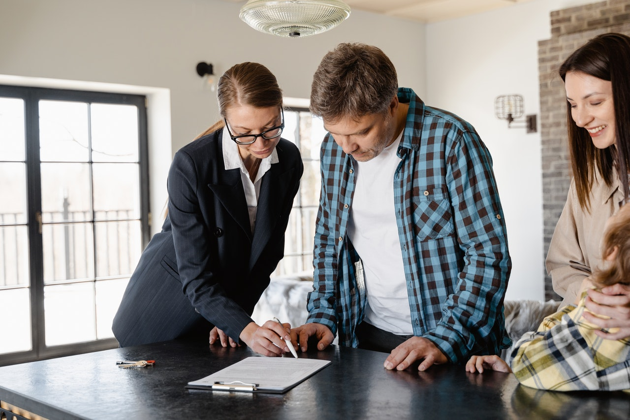 Real estate agent showing papers to potential buyers