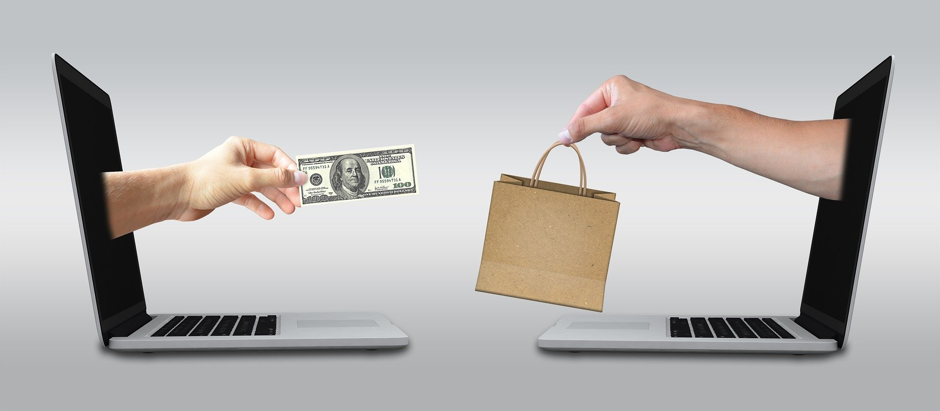 Two arms extending out from laptop screens and exchanging money with goods
